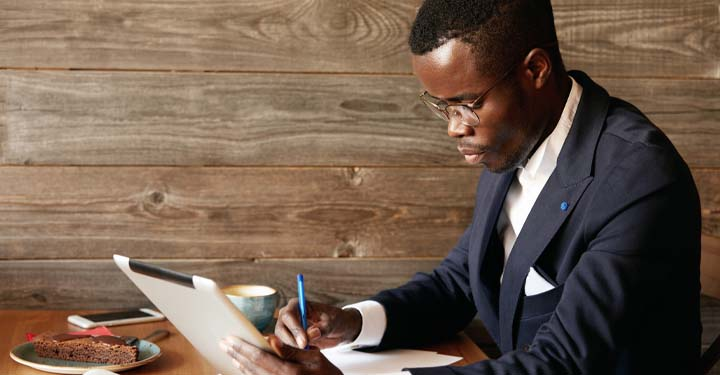 Suited man wearing glasses writing at a desk