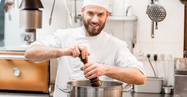 Chef putting pepper in a pot
