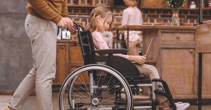 Little girl in a wheelchair using a laptop while a man pushes her through a kitchen